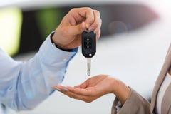 Bilförsäljare som räcker biltangenter till kvinnan arkivbilder