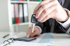 Bilförsäljare som rymmer en tangent och beräknar ett pris Royaltyfri Fotografi