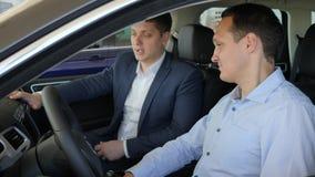 Bilförsäljning, sammanträde för ung man i bilen, pro-representantAdvises manlig klient i den motoriska showen, auto affär, lyckli stock video