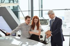 Bilförsäljningschef som berättar om särdragen av bilen till kunderna på återförsäljaren royaltyfri fotografi