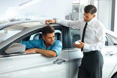 Bilförsäljningskonsulent Showing en ny bil till en potentiell köpare i S Royaltyfri Foto