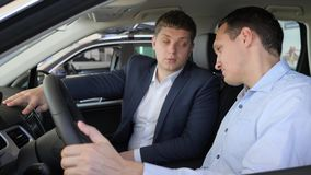 Bilförsäljningsmitt, ung man med den auto återförsäljaren i auto show eller salong lager videofilmer