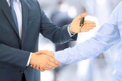 Bilförsäljare som räcker över tangenterna för en ny bil till en ung affärsman affärshandskakningfolk två Fokusera på ett nyckel- Fotografering för Bildbyråer