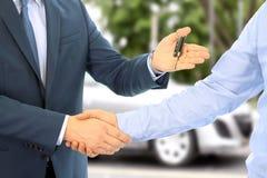 Bilförsäljare som räcker över tangenterna för en ny bil till en ung affärsman affärshandskakningfolk två Fokusera på ett nyckel- Arkivbilder