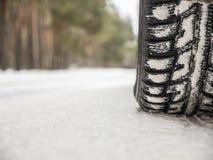 Bilgummihjul på vintervägen Arkivbilder