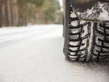 Bilgummihjul på vintervägen som täckas med snö Arkivfoto