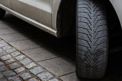 Bilgummihjulet vände trottoaren parkerade svarta vita Asphalt Road Dirty U Arkivbilder
