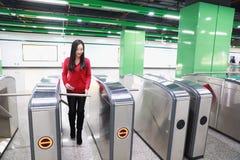 Bilhete da inserção da mulher ao estação de caminhos-de-ferro da entrada do bilhete fotografia de stock royalty free