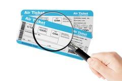 Bilhetes da passagem de embarque da linha aérea com vidro da lente de aumento à disposição Fotos de Stock