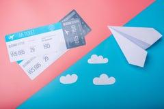 Bilhetes de ar e plano de papel no fundo pastel, topview Conceito da viagem aérea e dos feriados imagens de stock royalty free