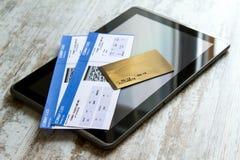 Bilhetes de avião de compra em uma tabuleta Fotos de Stock Royalty Free