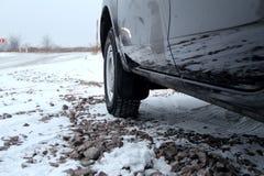 Bilhjul med vintergummihjulet på grusvägen på vintertid Royaltyfria Bilder