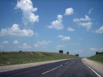 Bilhuvudvägen i sprickorna går långt in i avståndet på en ljus solig dag royaltyfri fotografi