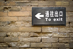 Bilingual exit sign. Black bilingual exit sign on grunge brick wall Stock Images
