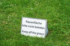 Bilingual keep of the grass sign in Germany Stock Photography