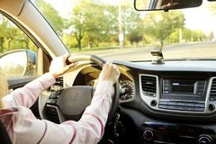 Bilinre med kvinnligt chaufförsammanträde bak hjulet, mjukt solnedgångljus Lyxig medelinstrumentbräda och elektronik fotografering för bildbyråer