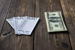 Biljetter av bookmakerkontors- och pengardollarna ligger på en trätabell, närbild arkivbild