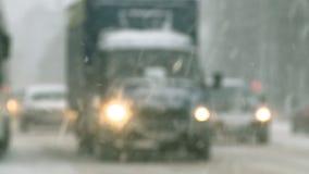 Bilkörning i staden under ett snöfall arkivfilmer