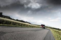 Bilkörning på den ensamma landsvägen Arkivbild