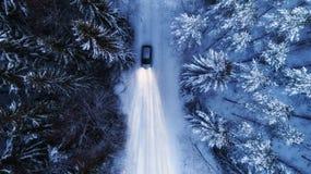 Bilkörning på den snöig landsvägen till och med vinterskog på natten H?g str?le p? arkivfoton