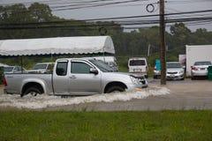 Bilkörning på en översvämmad väg i regnsäsong i ön Phuket Royaltyfri Fotografi