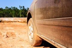 Bilkörning på grusvägar med dammapelsinen royaltyfri foto