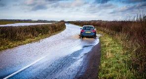 Bilkörning till och med den översvämmade vägen nära Nunney i Somerset, UK royaltyfri bild