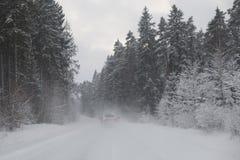Bilkörning till och med en snöig skog Arkivfoto