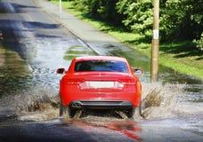 Bilkörning till och med floden bevattnar Royaltyfri Foto