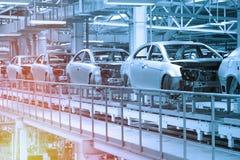 Bilkroppar är på monteringsband Fabrik för produktion av bilar i blått Modern bilindustri Blått tonar arkivfoto
