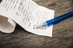 Bill e penna sulla tavola di legno Fotografia Stock