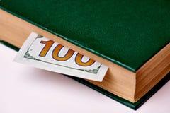 Bill en valeur cent dollars US dans le livre sur un macro blanc de fond photo stock