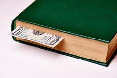 Bill en valeur cent dollars US dans le livre sur un macro blanc de fond image libre de droits