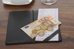 Bill mit Euroanmerkung über Tabelle Stockfotos