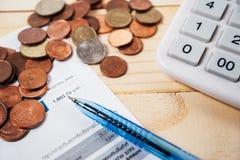 Bill mit Münzen und Stift und Taschenrechner auf Tabelle Lizenzfreie Stockfotografie