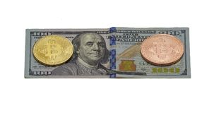 Gold and platinum coin Bitcoin lies on a hundred dollar bill. On the bill one hundred dollars are two coins of Bitcoin, gold and platinum Royalty Free Stock Photo