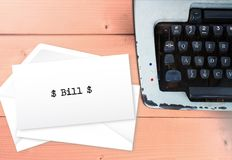 Bill text on envelops with typewriter. Vintage payment chaos concept on wooden table Stock Photos