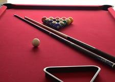 Billardkugeln auf einem roten Billardtisch mit zwei Stichwörtern, einem Gestell der schwarzen Kugel und einem weißen Spielball stockfotos