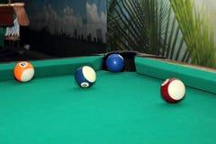 Billardkugeln auf grüner Tabelle und blauem Ball in der Tasche Stockbild