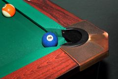 Billardkugeln auf grüner Tabelle und blauem Ball in der Tasche Lizenzfreie Stockbilder