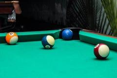 Billardkugeln auf grüner Tabelle und blauem Ball in der Tasche Stockbilder