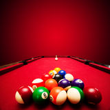 Billards pool game. Color balls in triangle, aiming at cue ball. Red cloth table Royalty Free Stock Photo