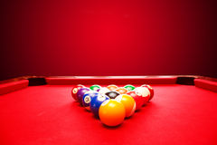 Billards pool game. Color balls in triangle. Red cloth table Stock Photos
