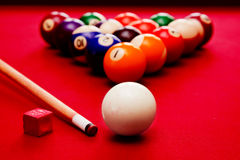 Billards pool game. Cue ball, cue color balls in triangle, chalk. Billards pool game. Cue ball, cue, color balls in triangle, chalk. Red cloth table Stock Images