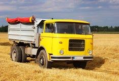 Billastbil på vetefältet som skördar Arkivfoton