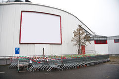 Billboard. A white building with a blank billboard and a lot of shopping trolley stock photo