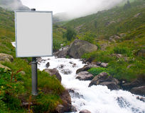 Billboard for advertising mounted next to a mountain stream in Royalty Free Stock Photography
