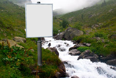 Billboard for advertising mounted next to a mountain stream in t Stock Photography