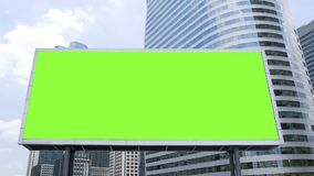 Billboard with a blank green screen mock-up in front of office building in business district on a busy day, time lapse. Footage for advertising background stock video footage