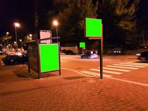 Billboard with a chroma key green screen on a traffic city night royalty free stock photography